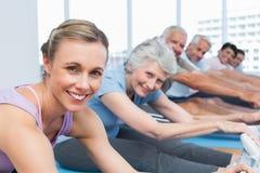 Classifichi l'allungamento delle mani alle gambe alla classe di yoga Immagine Stock