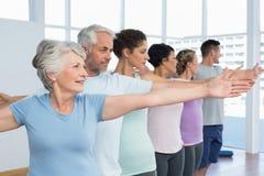 Classifichi l'allungamento delle mani nella fila alla classe di yoga Immagine Stock Libera da Diritti