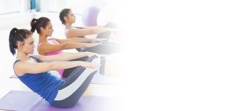 Classifichi l'allungamento sulle stuoie alla classe di yoga nello studio di forma fisica Immagini Stock