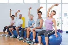 Classifichi la seduta sulle palle di esercizio e l'allungamento delle mani in palestra Fotografie Stock