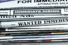 Classified ads. Stack of newspaper with Classified ads,immediate hiring,wanted signs royalty free stock photography