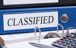 Classified - blue binder with text on desk in the office. With calculator and pen stock images