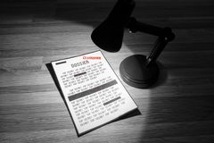 Classified dossier with redactions in a spotlight - Black and white. Photo of a classified dossier under a spotlight in black and white Stock Image