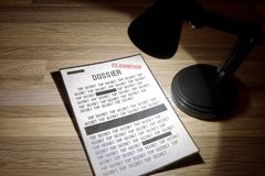 Classified, government dossier with redactions in a spotlight. Photo of a classified dossier under a lamp with words redacted Royalty Free Stock Images