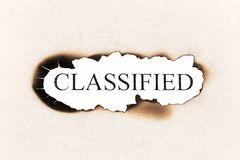 Classified word text. Appearing behind burned paper Stock Photos