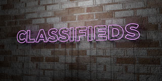 CLASSIFIEDS - Glowing Neon Sign on stonework wall - 3D rendered royalty free stock illustration. Can be used for online banner ads and direct mailers Royalty Free Stock Photo