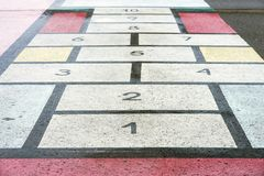 Classiic children game, hopscotch board drawn on asphalt, texture, modern creative background stock photos
