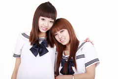 Classmate girls. Two beautiful schoolgirls in uniform on white,they are classmate royalty free stock photos