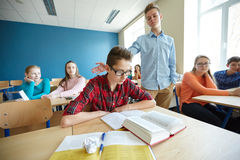 Classmate offending student boy at school. Education, bullying, social relations and people concept - classmate offending at student boy at school stock photos