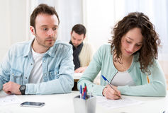 Classmate try to cheat on his neighbour. View of a Classmate try to cheat on his neighbour stock image