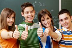 Classmates. Portrait of happy teens showing thumbs up Stock Photography
