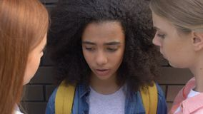 Classmates bullying biracial girl at wall, psychological attack, intimidation. Stock footage stock video
