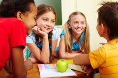 Classmates chatting. Portrait of joyful schoolchildren chatting in classroom stock photography