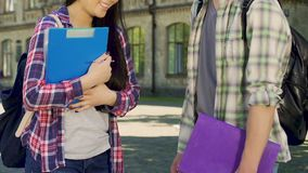Classmates with folders talking and laughing in front of university, education. Stock footage stock footage