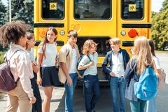 Classmates going to school standing near bus talking happy