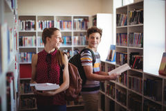 Classmates interacting while selecting book in library Stock Photo