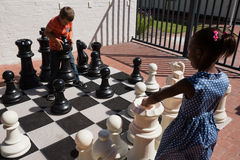 Classmates playing with large chess at school. On sunny day stock photography