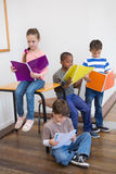 Classmates reading from notepads in classroom Royalty Free Stock Images