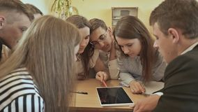 Classmates sit around the desk and discuss the school task with the tablet. Russian school. Classmates sit around the desk and discuss the school task with the stock footage