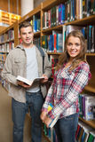 Classmates standing in library smiling at camera Stock Image