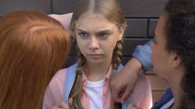 Classmates threatening weak girl at wall, demonstrating authority, threatening. Stock footage stock footage