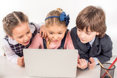 Classmates using laptop. Smiling classmates sitting at desk and using laptop Royalty Free Stock Photos