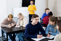 Classmates working in groups. Cheerful classmates and teacher working in groups to complete task during class royalty free stock images