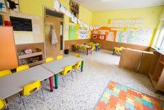 Classromm av dagiset med tabeller och små gula stolar Arkivbild