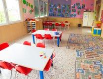 Classromm av dagiset med tabeller och små röda stolar Arkivbild