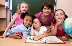 In the classroom. Portrait of teacher and children looking at camera in the classroom Royalty Free Stock Images