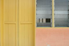Classroom. Exterior of classroom – missing window pane, yellow door and orange wall stock photo