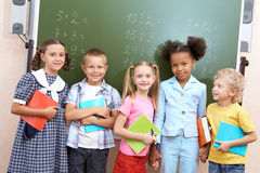 In the classroom. Image of curious schoolchildren standing by blackboard and looking at camera in the classroom Royalty Free Stock Photos