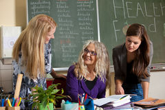 In the classroom. Teacher explaining something to two of her students Royalty Free Stock Photo