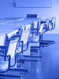 Classroom. Chairs in the classroom; blackboard on the background; blue tint Royalty Free Stock Image