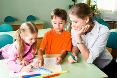 In the classroom. Image of confident teacher looking at girl�s picture with cute boy near by Stock Images