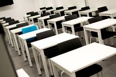 Classroom with black chairs and one blue chair. Hiring, vacant or choosing concept stock photos