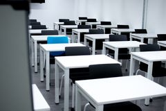 Classroom with black chairs and one blue chair. Hiring, vacant or choosing concept stock photo