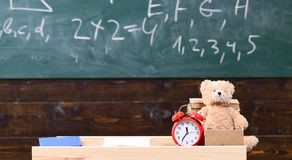 Classroom with chalkboard on background. Childish desk with alarm clock and teddy bear. Primary school concept. Classroom with table with books and copybook on stock photography