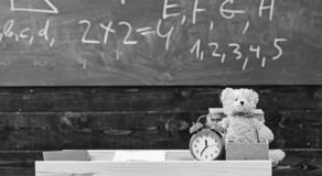 Classroom with chalkboard on background. Childish desk with alarm clock and teddy bear. Primary school concept. Classroom with table with books and copybook on stock photos