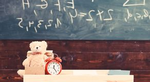 Classroom with chalkboard on background. Childish desk with alarm clock and teddy bear. Primary school concept. Classroom with table with books and copybook on stock images