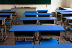 Classroom desks arranged in neat rows. Empty classroom with chairs, desks and chalkboard stock image