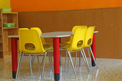 Classroom with desks and yellow chairs without kids. Kindergarten classroom with desks and yellow chairs without kids royalty free stock image