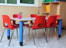 Classroom of a kindergarten with red chairs and small school tab Stock Images