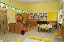 Classroom in a kindergarten with tables and yellow chairs Royalty Free Stock Images
