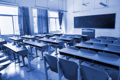 Classroom. Neat rows of school desks in classroom with blue tones stock images