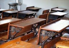 Classroom With Old Wooden Desks. School classroom with antique wooden desks with wrought iron decoration stock photos