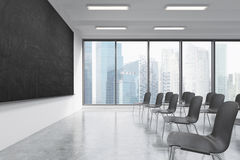 A classroom or presentation room in a modern university or fancy office. Black chairs, a black chalkboard on the wall and panorami Stock Photography