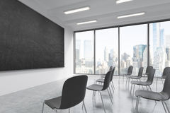 A classroom or presentation room in a modern university or fancy office. Black chairs, a black chalkboard on the wall and panorami Stock Images