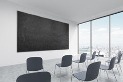 A classroom or presentation room in a modern university of fancy office. Black chairs, panoramic windows with New York view and a Royalty Free Stock Photography