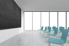 A classroom or presentation room in a modern university or fancy office. Blue chairs, panoramic windows with white copy space and. A black chalkboard on the Royalty Free Stock Image